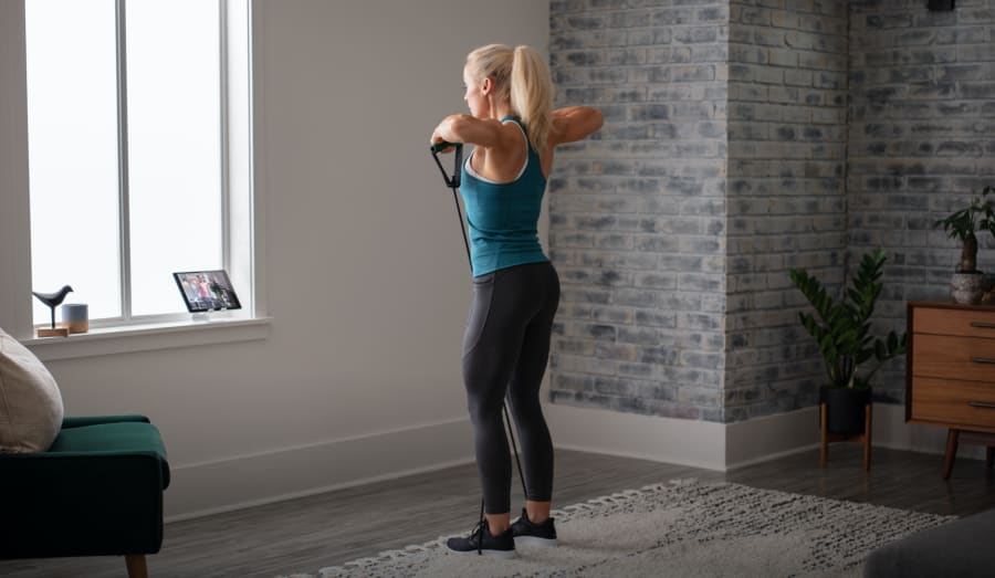 Woman working out using the Medium Resistance Tube.