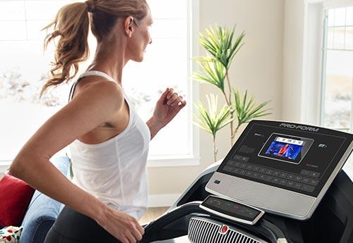 Woman running on the SMART Power 995i treadmill.